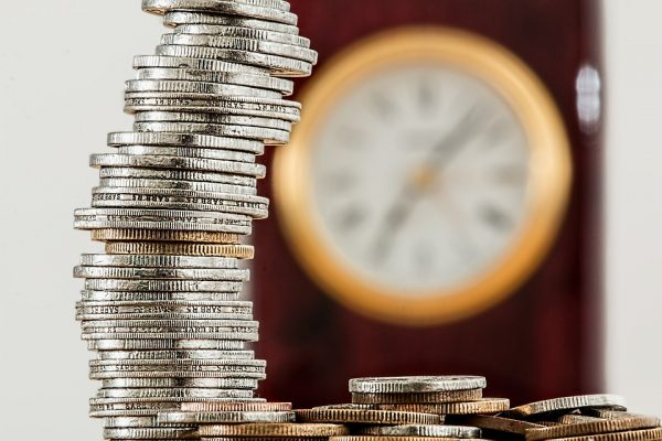 A stack of coins with a clock behind